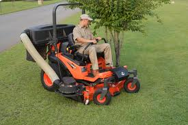 Mowing grass carefully around trees.